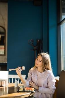 Молодая девушка в белом свитере ест суши на обед в небольшом кафе