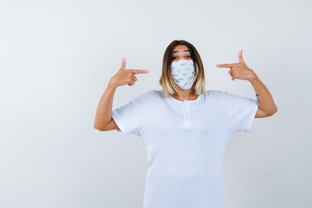 Молодая девушка в белой футболке и маске, указывая на себя указательными пальцами и уверенно глядя, вид спереди.