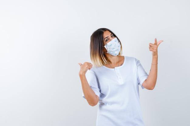 흰색 t- 셔츠와 검지 손가락으로 오른쪽과 왼쪽을 가리키는 마스크와 쾌활한, 전면보기를 찾고있는 어린 소녀.