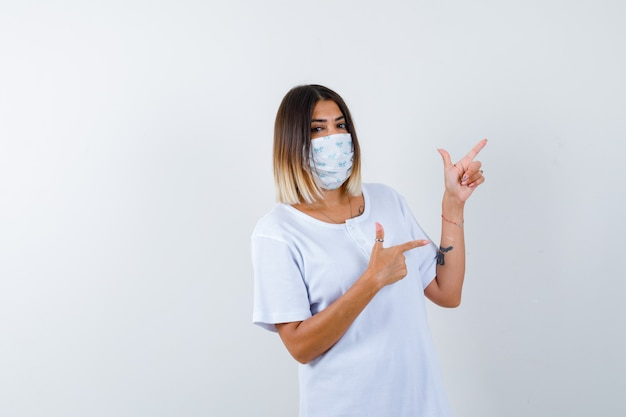 흰색 t- 셔츠와 마스크 오른쪽 검지 손가락으로 가리키고 자신감, 전면보기를 찾고있는 어린 소녀.