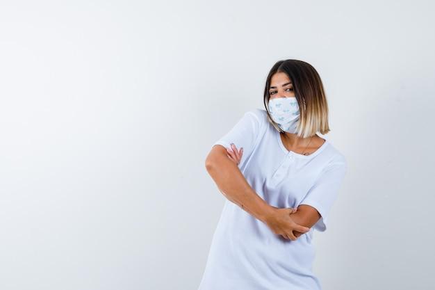 白いtシャツとマスクの立っている腕を組んで自信を持って見える、正面図の少女。