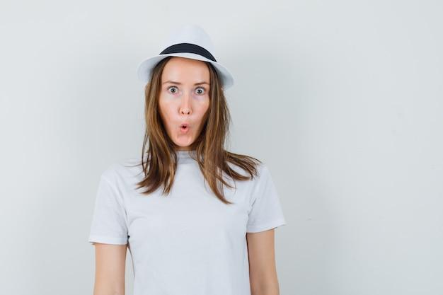 白いtシャツ、帽子、驚きの表情の少女。正面図。