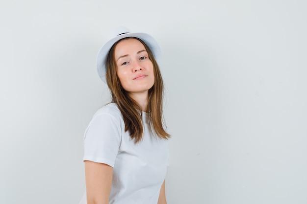 흰색 t- 셔츠, 모자 및 유혹 찾고 어린 소녀. 전면보기.