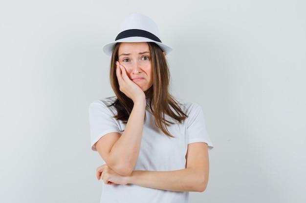 흰색 티셔츠에 어린 소녀, 손바닥에 뺨을 기울고 슬픈, 전면보기를 찾고 모자.