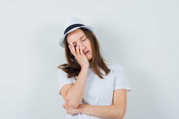 흰색 t- 셔츠, 제기 손바닥에 뺨을 기울고 모자와 졸린, 전면보기를 찾고있는 어린 소녀.