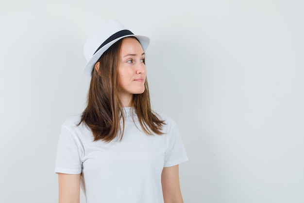 白いtシャツを着た少女、脇を向いて優雅に見える帽子、正面図。