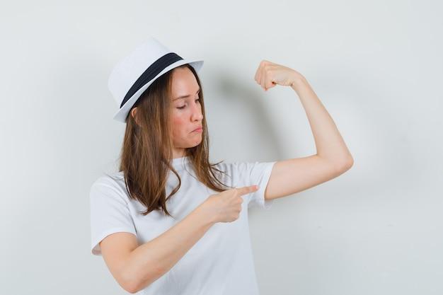 Молодая девушка в белой футболке, шляпе, указывающей на мышцы руки и гордой, вид спереди.