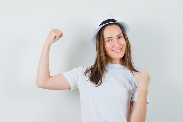 Молодая девушка в белой футболке, шляпе, показывающей жест победителя и веселой, вид спереди.