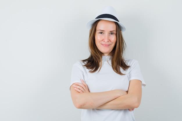흰색 t- 셔츠, 교차 팔으로 서 서 자신감, 전면보기 모자에 어린 소녀.