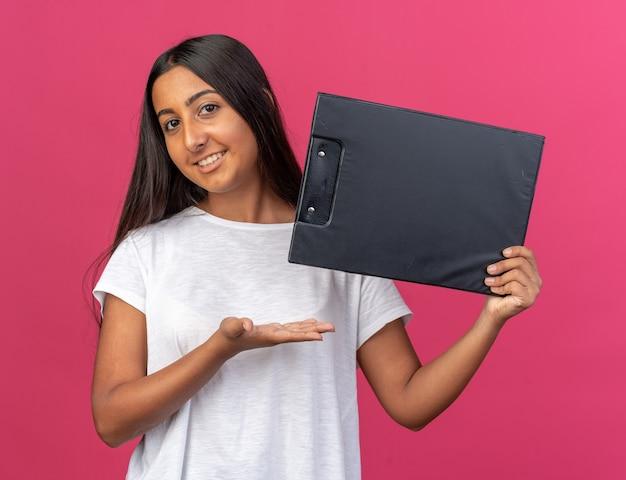 클립보드를 들고 있는 흰색 티셔츠를 입은 어린 소녀가 분홍색 배경 위에 손을 들고 즐겁게 웃고 있는 카메라를 바라보고 있습니다.