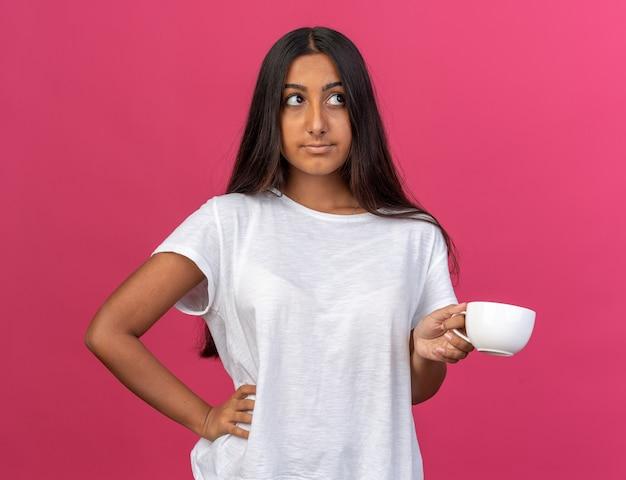 ピンクの上に立って困惑して見上げるコーヒーのカップを保持している白いtシャツの少女
