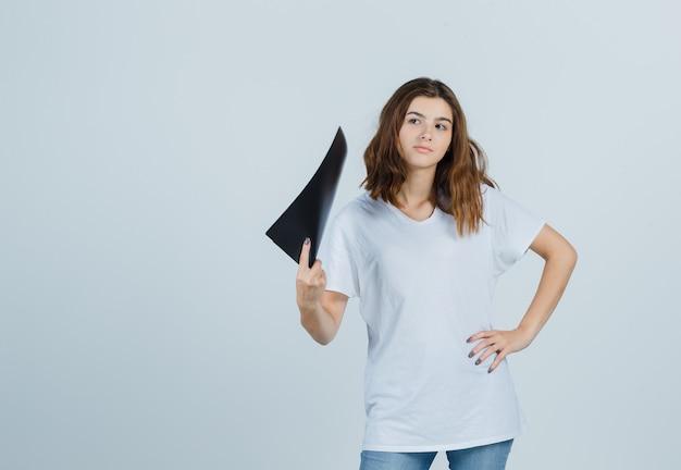 Молодая девушка в белой футболке, держа папку и задумчиво, вид спереди.