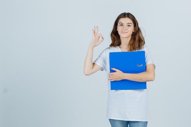Молодая девушка в белой футболке, держащей папку, показывая хорошо жест и весело, вид спереди.
