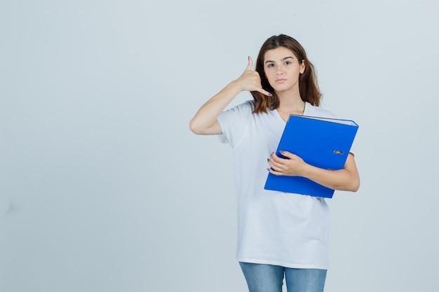 Молодая девушка в белой футболке держит папку, показывает жест телефона и выглядит полезным, вид спереди.