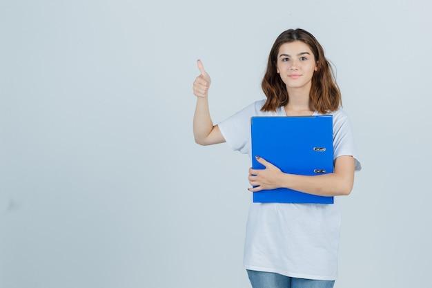 Молодая девушка в белой футболке, держащей папку, показывая большой палец вверх и весело, вид спереди.
