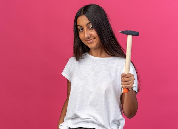 흰색 티셔츠를 입은 어린 소녀가 해머를 들고 분홍색 배경 위에 서 있는 얼굴에 미소를 띠고 카메라를 바라보고 있습니다.