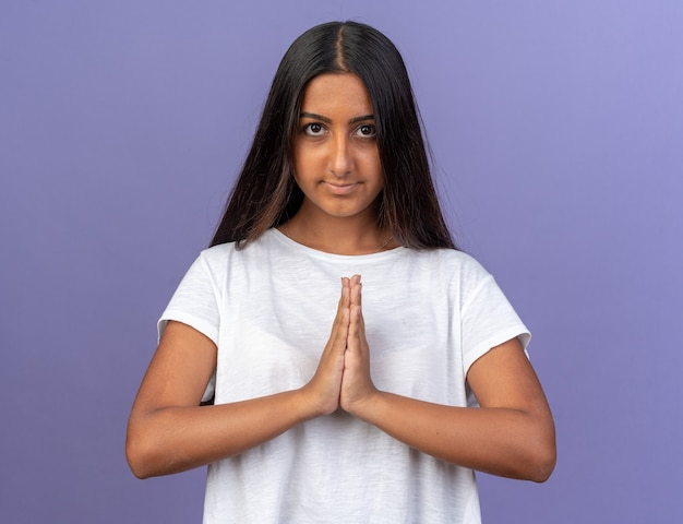 Молодая девушка в белой футболке, взявшись за руки, как жест намасте, смотрит в камеру с улыбкой на лице