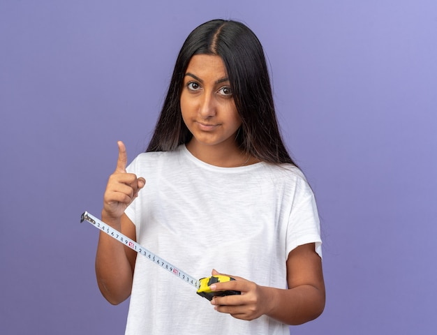 검지 손가락 경고 제스처를 보여주는 심각한 얼굴로 카메라를보고 측정 테이프를 들고 흰색 티셔츠에 어린 소녀