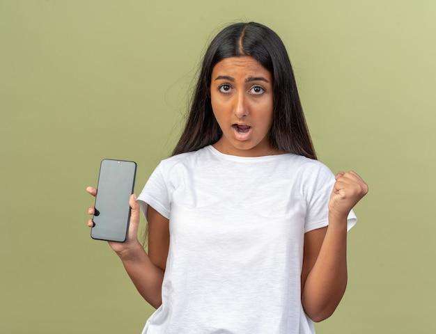 Молодая девушка в белой футболке держит смартфон, глядя в камеру, смущенная и недовольная сжимая кулак
