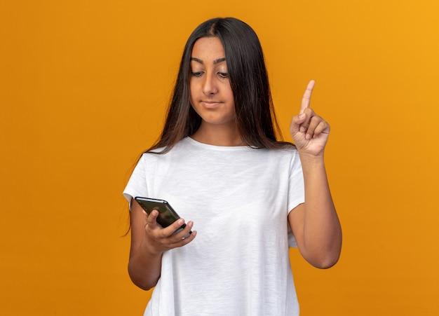 스마트폰을 들고 스마트폰을 들고 있는 어린 소녀는 주황색 배경 위에 새로운 아이디어가 서 있는 검지 손가락을 보여주는 똑똑한 얼굴에 미소를 지으며 스마트폰을 보고 있습니다.