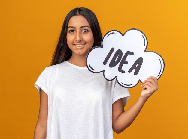Молодая девушка в белой футболке держит знак речи пузырь с идеей слова, глядя в камеру