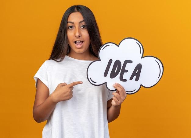 Молодая девушка в белой футболке держит знак речи пузырь с идеей слова, указывая указательным пальцем
