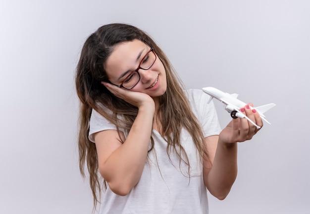 夢のような表情でそれを見ているおもちゃの飛行機を保持している白いtシャツの少女