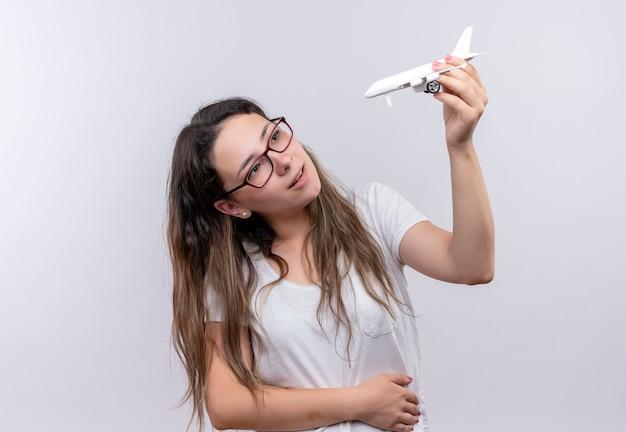 おもちゃの飛行機を持っている白いtシャツの少女は、おもちゃで楽しく幸せそうに見えます
