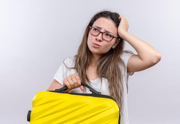 Молодая девушка в белой футболке с дорожным чемоданом смотрит в сторону, смущенная рукой за голову