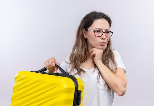 顔に物思いにふける表情で脇を見て旅行スーツケースを保持している白いtシャツの少女