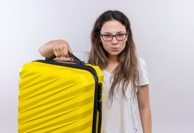 眉をひそめている顔に不満を持ってカメラを見て旅行スーツケースを保持している白いtシャツの少女