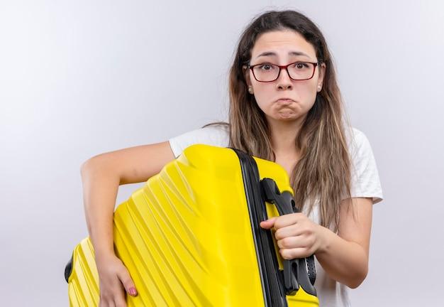 Молодая девушка в белой футболке с дорожным чемоданом смотрит в камеру с грустным выражением лица и несчастным лицом