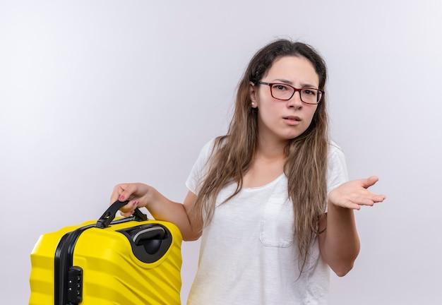 手のひらを広げることに疑いを持って混乱しているように見える旅行スーツケースを保持している白いtシャツの少女