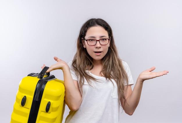 不確かで混乱している手のひらを広げて見える旅行スーツケースを保持している白いtシャツの少女