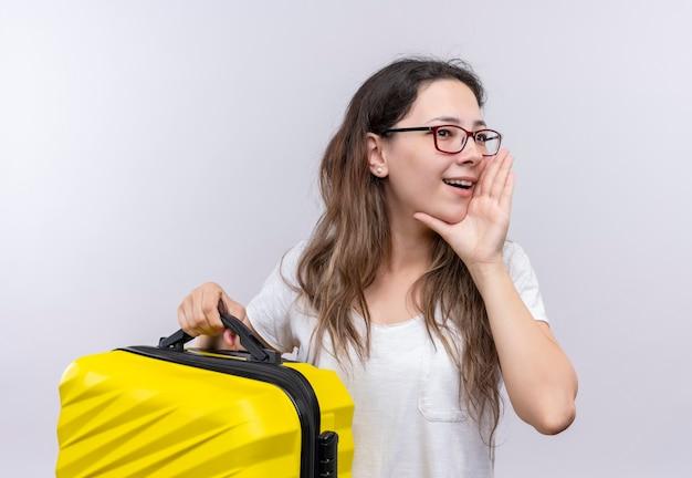 Молодая девушка в белой футболке держит дорожный чемодан, кричит или зовет кого-то рукой возле рта