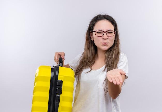 眉をひそめているカメラを見てカメラに腕を示す旅行スーツケースを保持している白いtシャツの少女