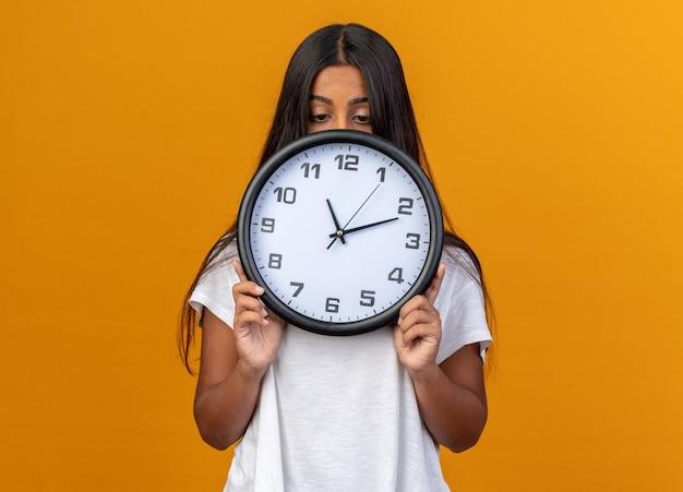 주황색 배경 위에 서 있는 벽시계 뒤에 얼굴을 숨기고 있는 흰색 티셔츠를 입은 어린 소녀