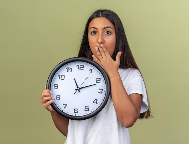 손으로 입을 덮고 충격을 받고 카메라를보고 벽 시계를 들고 흰색 티셔츠에 어린 소녀
