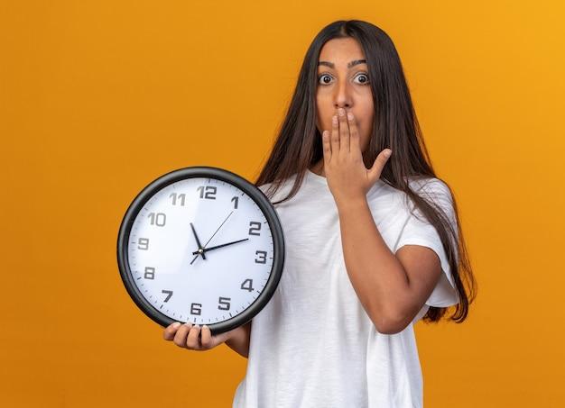 입을 덮고 충격을 받고 카메라를보고 벽 시계를 들고 흰색 티셔츠에 어린 소녀