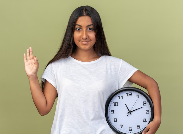 확인 표시를하고 얼굴에 미소로 카메라를보고 벽 시계를 들고 흰색 티셔츠에 어린 소녀
