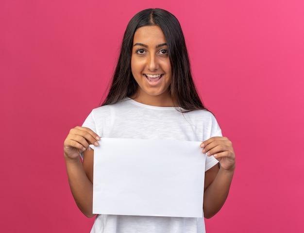 Молодая девушка в белой футболке держит белый чистый лист бумаги, глядя в камеру с улыбкой на лице, стоя над розовым