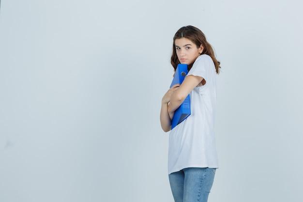Молодая девушка в белой футболке обнимает папку и смущенно смотрит, вид спереди.