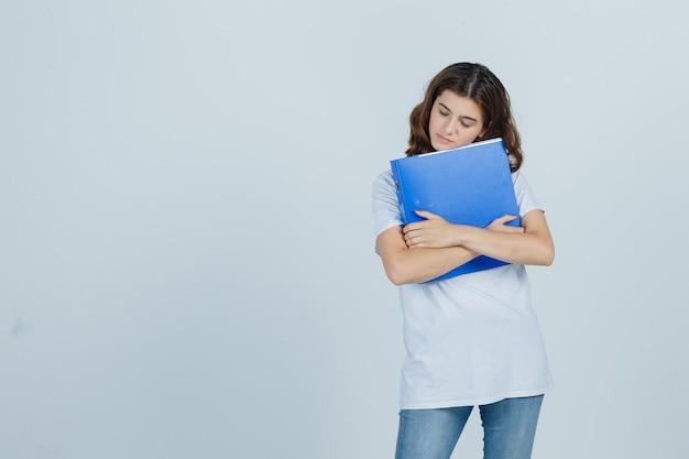 Молодая девушка в белой футболке обнимает папку и смотрит мирно, вид спереди.