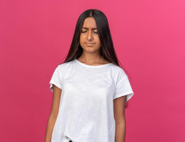 ピンクの上に立ってイライラしてイライラして見える白いtシャツの少女