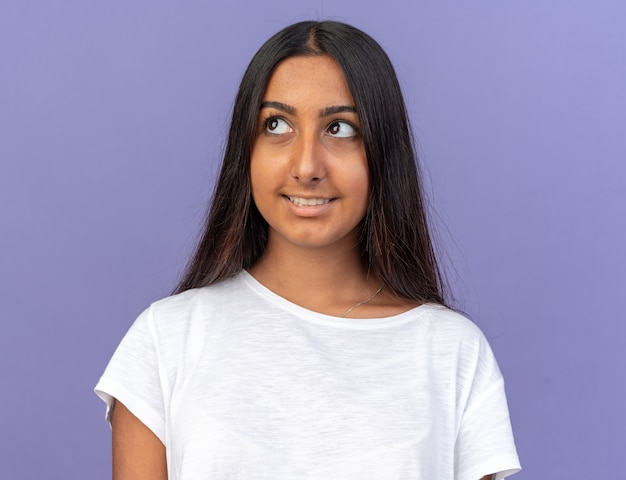 Молодая девушка в белой футболке смотрит в сторону с улыбкой на счастливом лице, стоящем над синим
