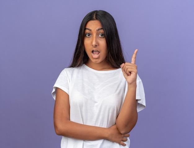 카메라를 보고 있는 흰색 티셔츠를 입은 어린 소녀는 파란색 배경 위에 서 있는 새로운 아이디어를 가진 검지 손가락을 보여 놀라고 놀랐습니다.