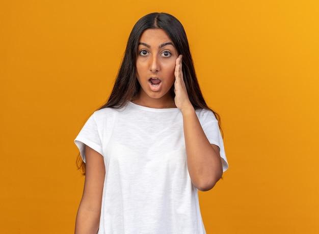 Молодая девушка в белой футболке смотрит в камеру изумленно и удивленно, стоя на оранжевом фоне