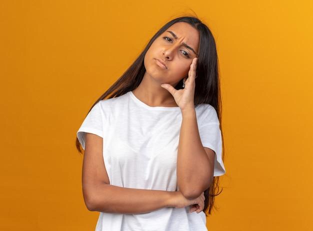 카메라를 쳐다보는 흰색 티셔츠를 입은 어린 소녀가 오렌지색 배경 위에 서 있는 것이 싫고 지겹다