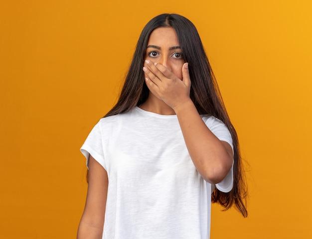 オレンジ色の背景の上に立っている手で口を覆ってショックを受けているカメラを見ている白いtシャツの少女