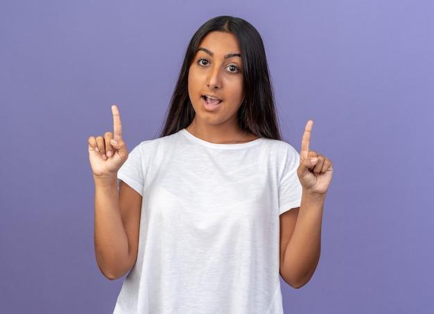 Молодая девушка в белой футболке смотрит в камеру, счастливая и удивленная, показывая указательные пальцы с новой идеей